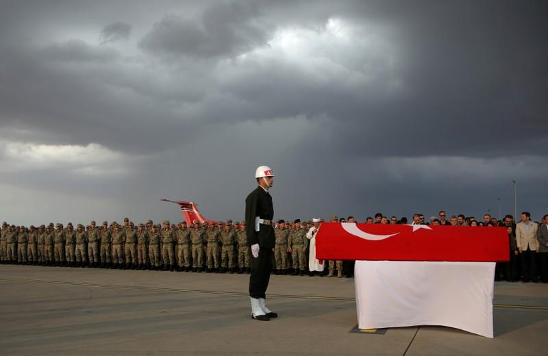 FILE PHOTO: Honour guard stands in front of the flag-wrapped coffin of Turkish soldier Findik during a ceremony at the GAP Airport in Sanliurfa