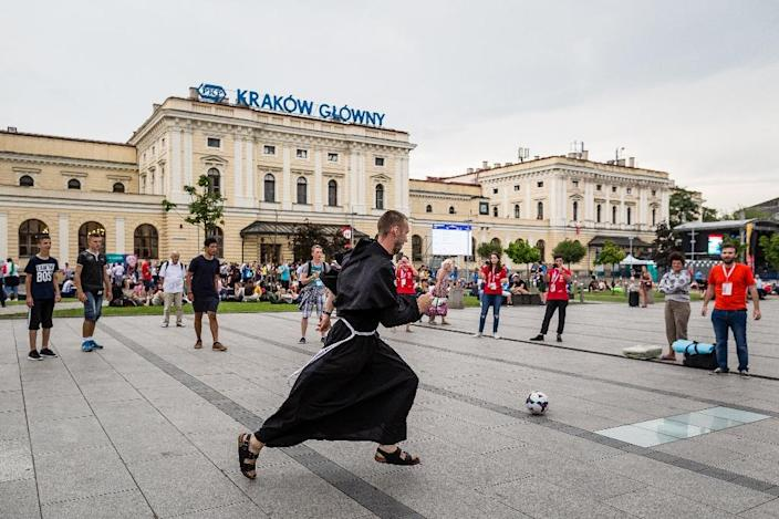 Young people and a monk play football in Krakow, Poland, on July 25, 2016, one day ahead of the opening of the World Youth Day to be attended by Pope Francis (AFP Photo/Wojtek Radwanski)