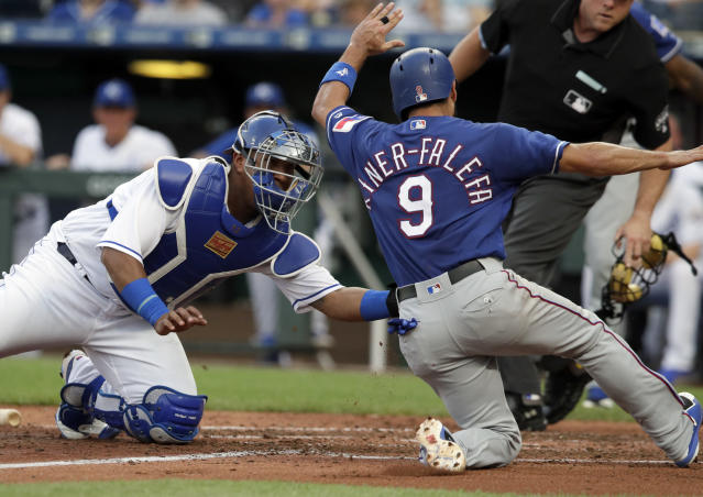 Kansas City Royals catcher Salvador Perez, left, tags out Texas Rangers' Isiah Kiner-Falefa (9) during the third inning of a baseball game at Kauffman Stadium in Kansas City, Mo., Tuesday, June 19, 2018. (AP Photo/Orlin Wagner)