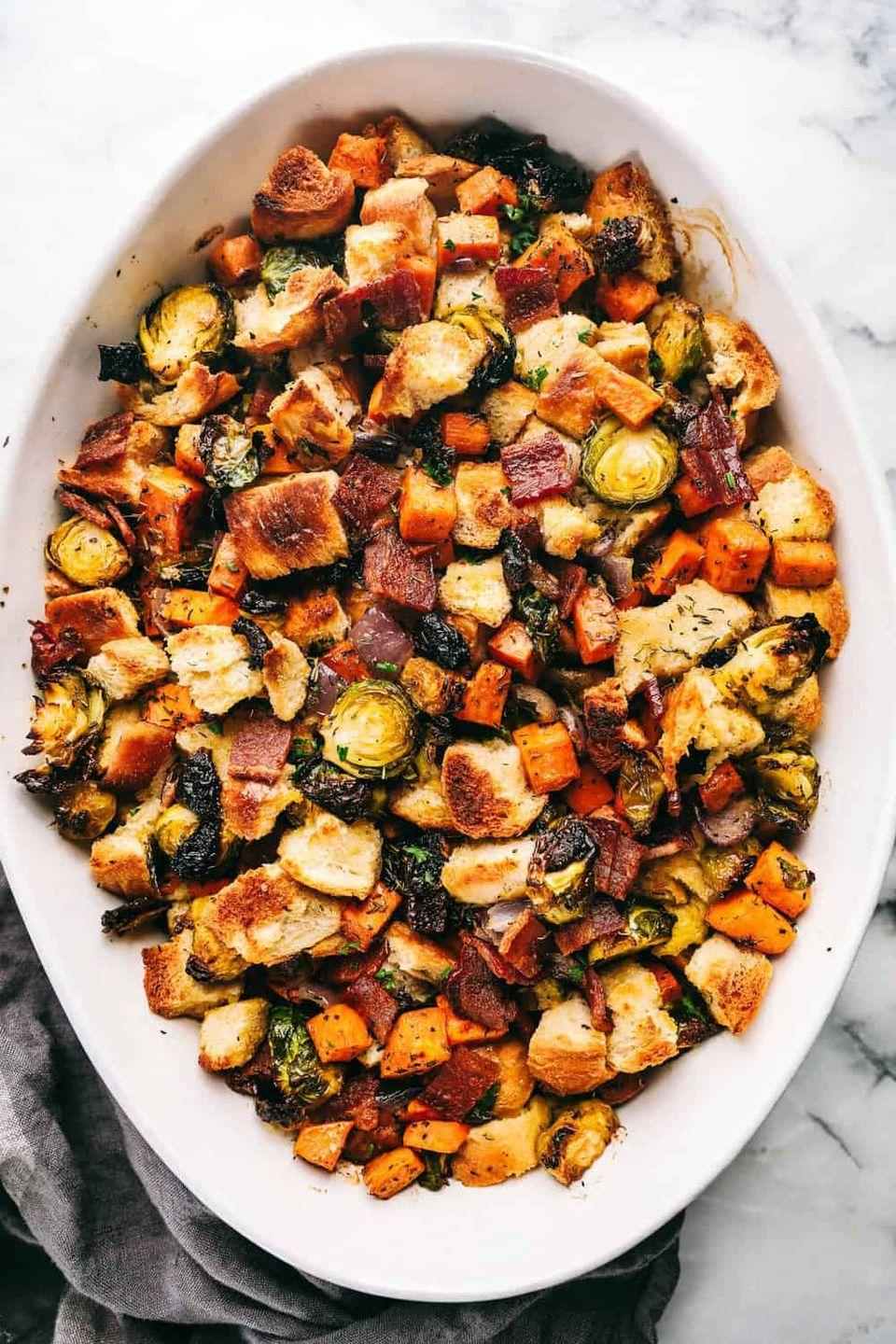"<p>Loaded with <a href=""https://www.countryliving.com/food-drinks/g877/sweet-potato-recipes-1009/"" rel=""nofollow noopener"" target=""_blank"" data-ylk=""slk:sweet potato"" class=""link rapid-noclick-resp"">sweet potato</a>, <a href=""https://www.countryliving.com/food-drinks/g4685/acorn-squash/"" rel=""nofollow noopener"" target=""_blank"" data-ylk=""slk:acorn squash"" class=""link rapid-noclick-resp"">acorn squash</a>, and bacon, this <a href=""https://www.countryliving.com/food-drinks/g908/stuffing-recipes/"" rel=""nofollow noopener"" target=""_blank"" data-ylk=""slk:stuffing recipe"" class=""link rapid-noclick-resp"">stuffing recipe</a> is ultra hearty. You'll never consider making a boxed version again after trying this.</p><p><strong>Get the recipe at <a href=""https://therecipecritic.com/roasted-autumn-vegetable-stuffing/"" rel=""nofollow noopener"" target=""_blank"" data-ylk=""slk:The Recipe Critic"" class=""link rapid-noclick-resp"">The Recipe Critic</a>.</strong> </p>"