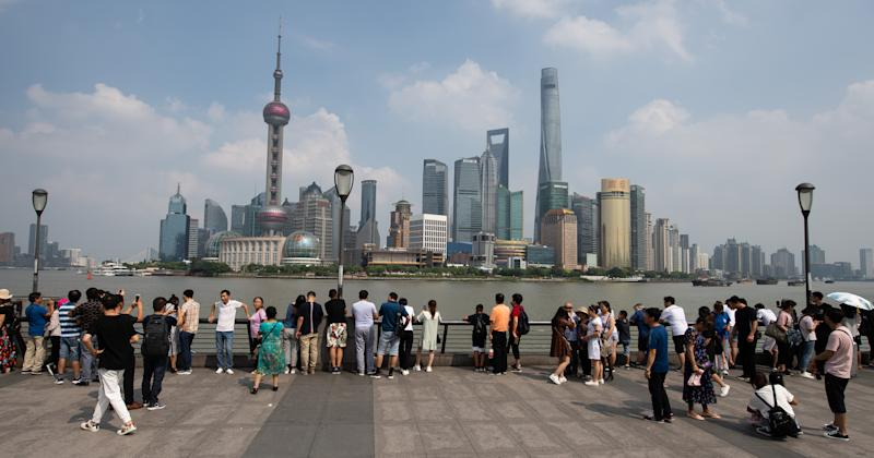 "08 September 2019, China, Shanghai: Tourists stand at the promenade ""The Bund"" at the Huangpu river with a view of the skyline of the special economic zone Pudong with its skyscrapers. On the left you can see the Oriental Pearl Tower and on the right the Shanghai Tower. Photo: Swen Pförtner/dpa (Photo by Swen Pförtner/picture alliance via Getty Images)"