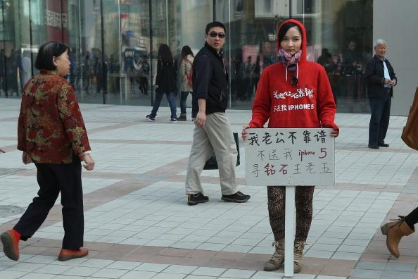 "BEIJING, CHINA - OCTOBER 20:  A Chinese woman holds a sign which reads ""My husband is not reliable, he doesn't buy me an iPhone 5, I'm looking for a rich man"" outside a newly opened Apple Store in Wangfujing shopping district on October 20, 2012 in Beijing, China. Apple Inc. opened its sixth retail store on the Chinese mainland Saturday. The new Wangfujing store is Apple's largest retail store in Asia.  (Photo by Feng Li/Getty Images)"