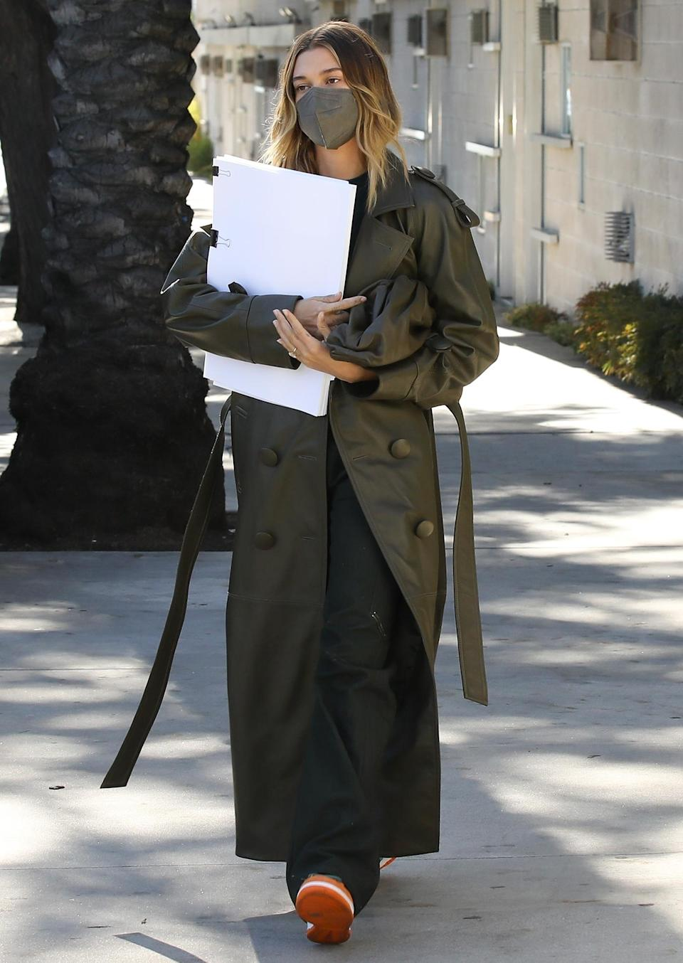 <p>Hailey Bieber walks out of a meeting in a long trench coat and a matching mask on Tuesday in L.A.</p>