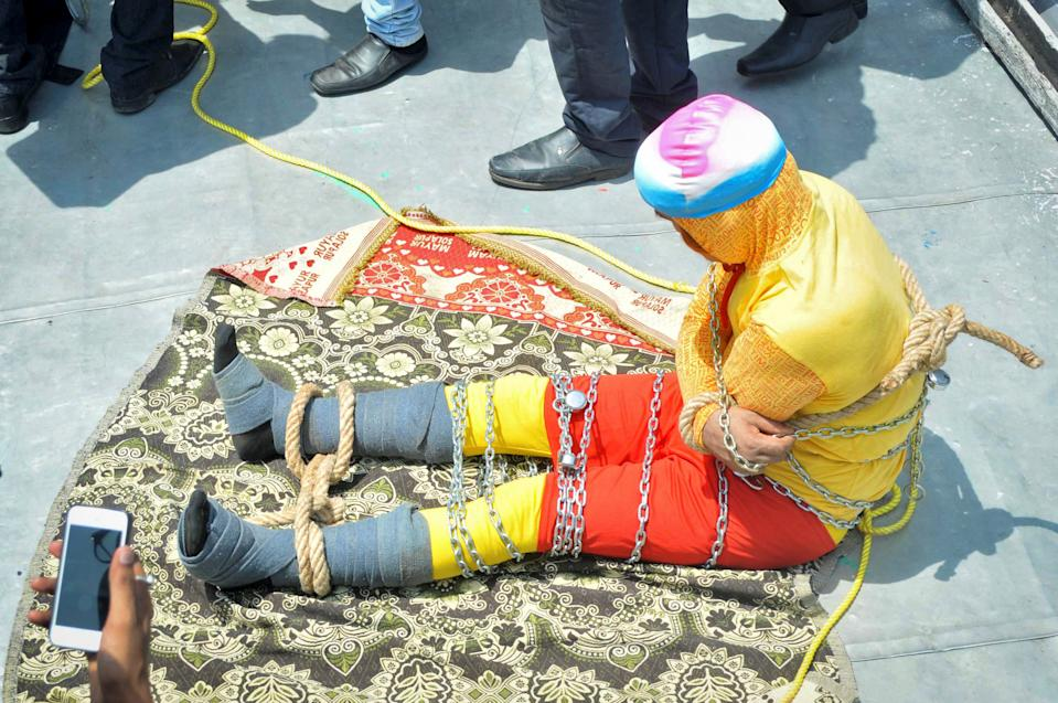 Pictured is a chained up Chanchal Lahiri. He was lowered into India's Hooghly river on Sunday for a magic trick but was found dead the day after.