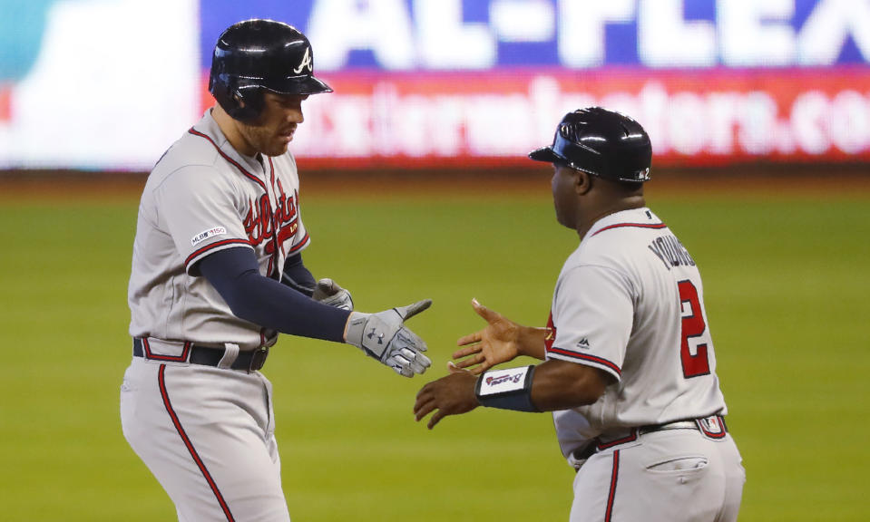 Atlanta Braves' Freddie Freeman, left, is congratulated by first base coach Eric Young (2) after Freeman got a base hit during the first inning of a baseball game against the Miami Marlins, Sunday, June 9, 2019, in Miami. (AP Photo/Wilfredo Lee)