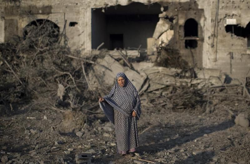 A Palestinian woman gestures as she stands amidst destruction following an Israeli military strike in Gaza City on July 8, 2014 (AFP Photo/Mahmud Hams)