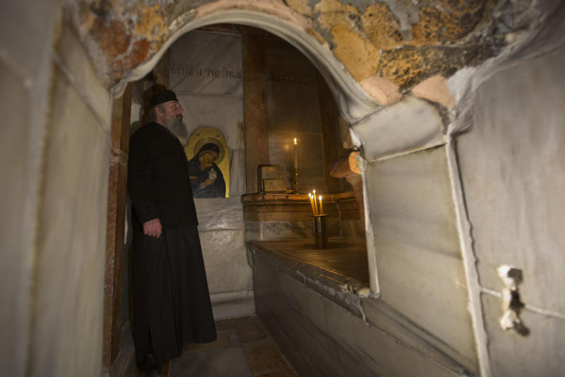 A Greek priest stands inside the renovated Edicule in the Church of the Holy Sepulchre, traditionally believed to be the site of the crucifixion of Jesus Christ, in Jerusalem's old city Monday, Mar. 20, 2017. A Greek restoration team has completed a historic renovation of the Edicule, the shrine that tradition says houses the cave where Jesus was buried and rose to heaven. (AP Photo/Sebastian Scheiner)