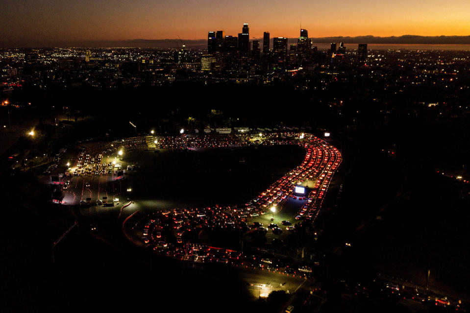 "FILE - In this Nov 18, 2020, file aerial photo, motorists wait in long lines to take a coronavirus test in a parking lot at Dodger Stadium in Los Angeles. The Los Angeles County has announced a new stay-home order as coronavirus cases surge out of control in the nation's most populous county. The three-3 week order take effect Monday, Nov. 30, 2020. The order advises residents to stay home ""as much as possible"" and to wear a face covering when they go out. It bans people from gathering with people who aren't in their households, whether publicly or privately. (AP Photo/Ringo H.W. Chiu, File)"