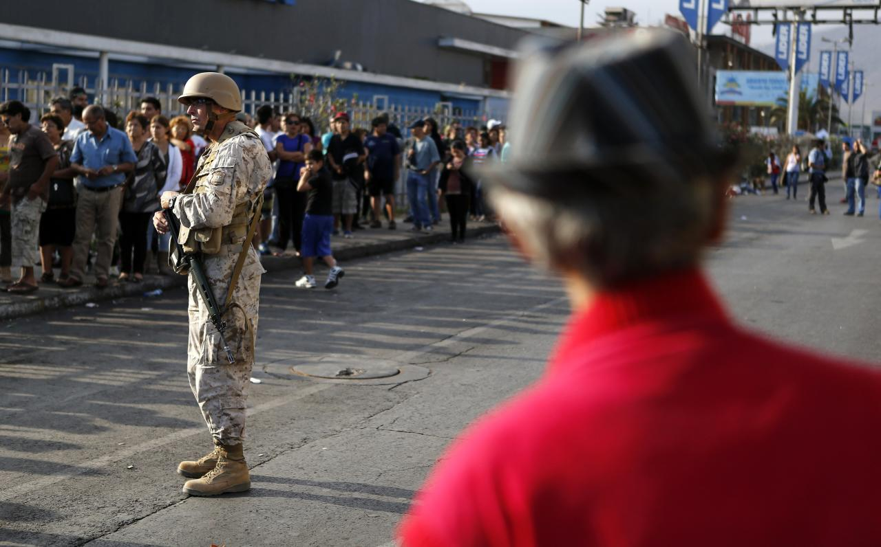 A soldier stands guard as people line up outside a supermarket after a series of aftershocks in the northern port of Iquique April 3, 2014. As the aftershocks from a massive 8.2 magnitude quake that rattled northern Chile entered a third day on Thursday, basic services were still out in the port city nearest the epicenter and residents fearful of tsunamis were fleeing into the hills. The quake on Tuesday was blamed for six deaths and residents have been hit by dozens of aftershocks, including a powerful 7.6 magnitude quake on Wednesday night. Both quakes triggered tsunami warnings and evacuations. REUTERS/Ivan Alvarado (CHILE - Tags: DISASTER SOCIETY ENVIRONMENT)