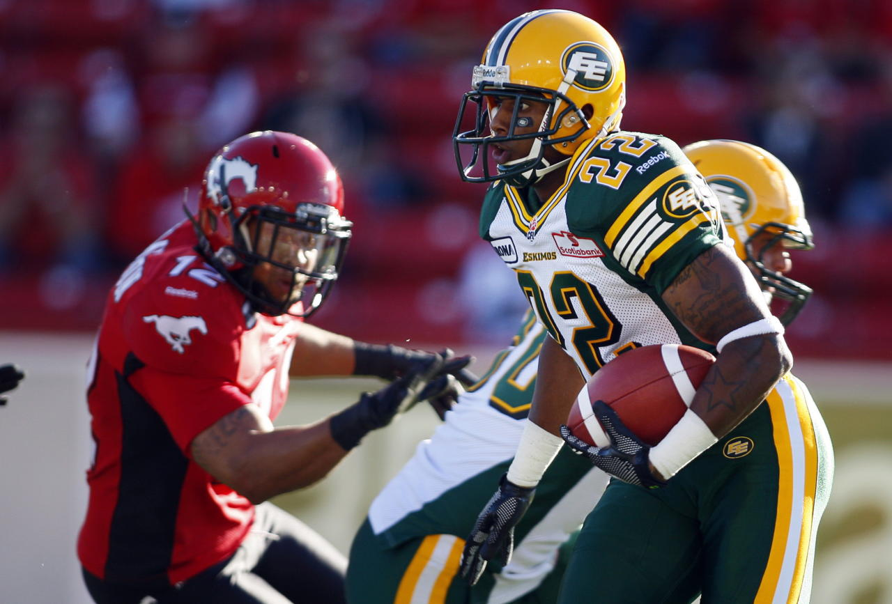 Edmonton Eskimos' Joe Burnett, centre, runs the ball during first half CFL pre-season football action against the Calgary Stampeders in Calgary, Alta., Friday, June 15, 2012. THE CANADIAN PRESS/Jeff McIntosh