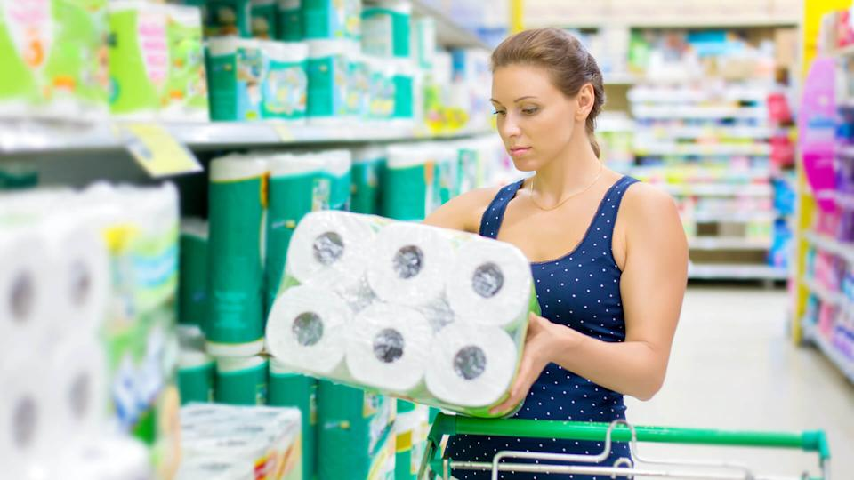 woman buys toilet paper in the supermarket.