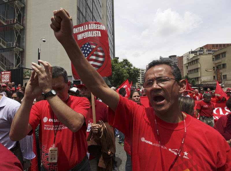Employees of Petroleos de Venezuela, or PDVSA, shout slogans against the United States during a protest outside the main offices in Caracas, Venezuela, Wednesday, May 25, 2011. President Hugo Chavez's government condemned U.S. sanctions imposed on Venezuela's state oil company for doing business with Iran, saying it is evaluating how fuel shipments might be affected. (AP Photo/Fernando Llano)
