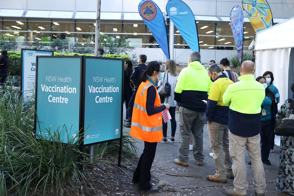 People are seen queuing to enter a mass Covid-19 vaccination hub in Sydney, Australia.
