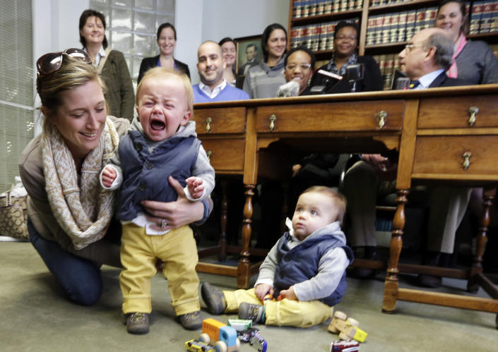 Amanda Broughton, left, comforts one of her two twin sons while her partner Michele Hobbs, top left, stands behind her Monday, Feb. 10, 2014, during a news conference in Cincinnati. Four legally married gay couples filed a federal civil rights lawsuit Monday seeking a court order to force Ohio to recognize same-sex marriages on birth certificates despite a statewide ban. Broughton is the birth mother of the twins. (AP Photo/Al Behrman)