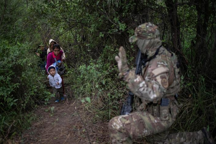A member of the U.S. Border Patrol Tactical Unit waves to a family that illegally crossed the Rio Grande river to enter the U.S. from Mexico in Fronton, Texas, on Oct. 18, 2018. (Photo: Adrees Latif/Reuters)
