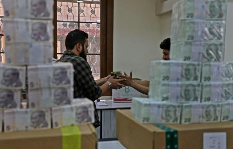 Employees sort Turkish lira banknotes at a bank in the town of Sarmada in Syria's northwestern Idlib province