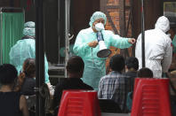Medical personnel wearing protective gear, guide people at a rapid coronavirus testing center after the infection alert rose to level 3 in Taipei, Taiwan, Tuesday, May 18, 2021. (AP Photo/Chiang Ying-ying)