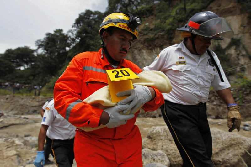 A rescuer carries the body of a baby, victim of a bus crash, in San Martin Jilotepeque, Chimaltenango region