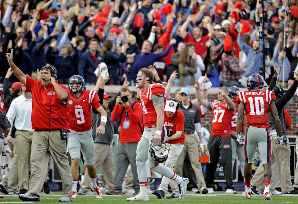 Mississippi quarterback Bo Wallace, center, reacts after the official calls for a Mississippi touchdown on a review during the first half of an NCAA college football game against Mississippi State in Oxford, Miss., Saturday, Nov. 29, 2014. (AP Photo/Thomas Graning)