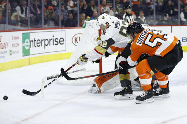 Vegas Golden Knights' Tomas Nosek (92) and Philadelphia Flyers' Shayne Gostisbehere (53) vie for the puck during the first period of an NHL hockey game Monday, Oct. 21, 2019, in Philadelphia. (AP Photo/Matt Rourke)