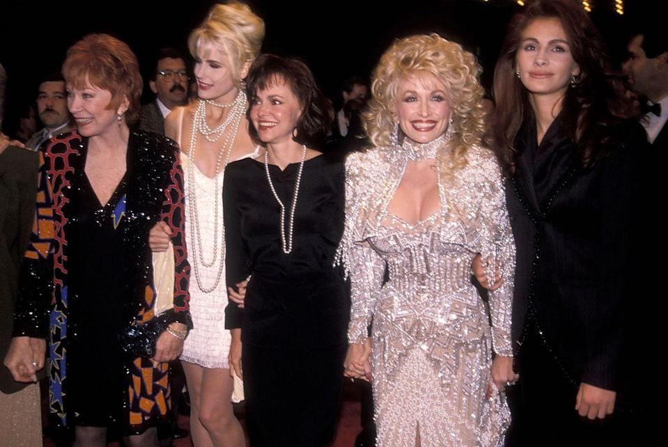 <p>Parton and an all-star cast consisting of Shirley MacLaine, Daryl Hannah, Sally Fields, and Julia Roberts shine at an event promoting <em>Steel Magnolias. </em>An all-white, beaded dress ensures Dolly stands out like no one else. </p>