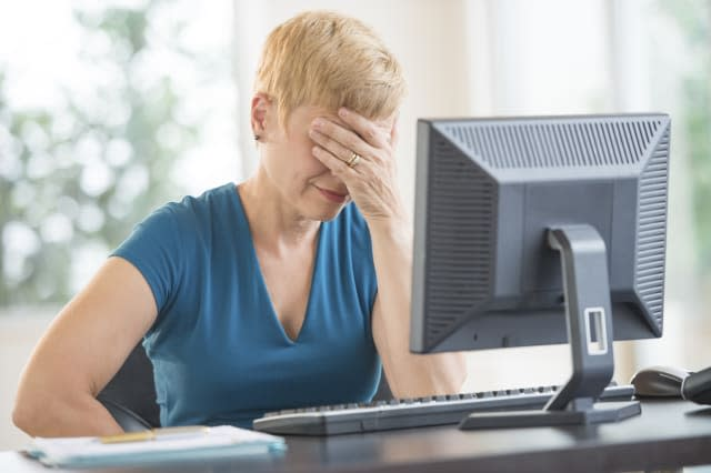 Tired Businesswoman Leaning On Computer Desk