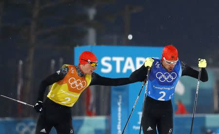 Nordic Combined Events - Pyeongchang 2018 Winter Olympics - Men's Team 4 x 5 km Final - Alpensia Cross-Country Skiing Centre - Pyeongchang, South Korea - February 22, 2018 - Eric Frenzel of Germany and Johannes Rydzek of Germany exchange. REUTERS/Kai Pfaffenbach