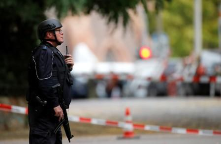 A police officer stands next to the site of a shooting in Halle