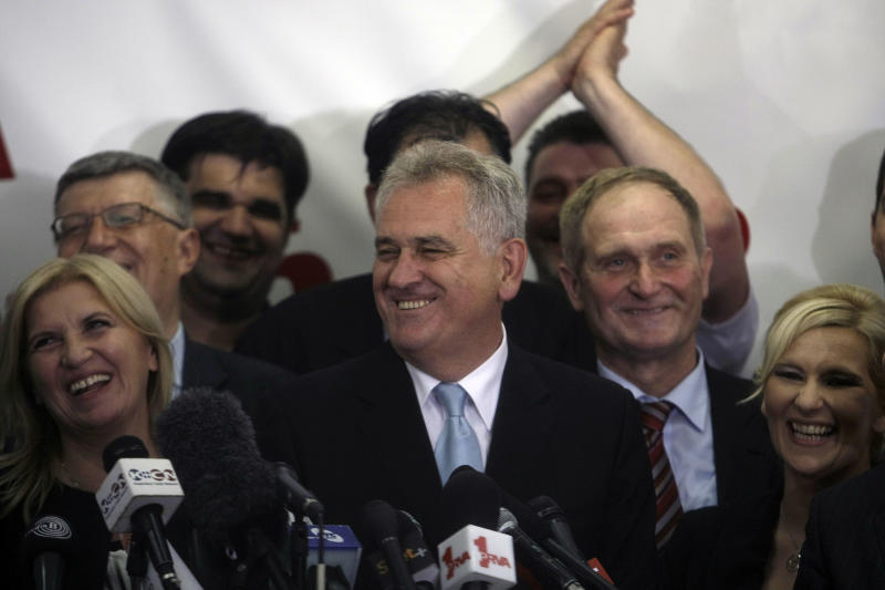 Tomislav Nikolic, center, the nationalist Serbian Progressive Party leader and presidential candidate, smiles as he talks to members of the media after claiming victory at the presidential runoff elections in Belgrade, Serbia, Sunday, May 20, 2012, with his wife, Dragica at left. Nationalist Nikolic beat pro European Union incumbent Boris Tadic in Serbia's presidential runoff election. (AP Photo/ Marko Drobnjakovic)