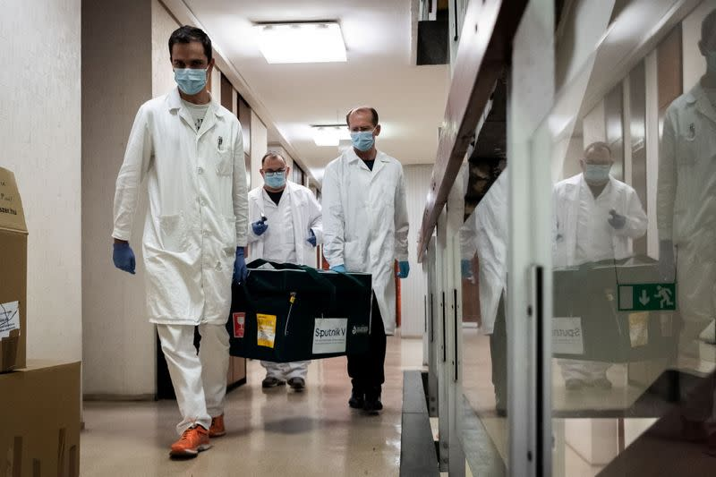 "Laboratory assistants carry a bag with Russia's ""Sputnik-V"" vaccine against the coronavirus disease (COVID-19) at the National Institute of Pharmacy and Nutrition in Budapest"