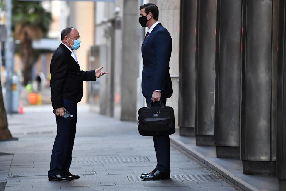 Barrister Bruce McClintock greets Roberts-Smith outside the court on Monday