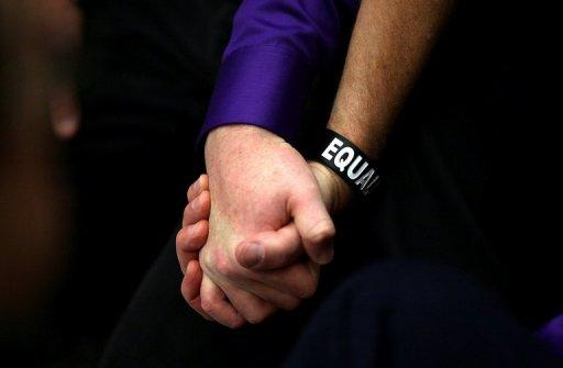 A same-sex couple hold hands