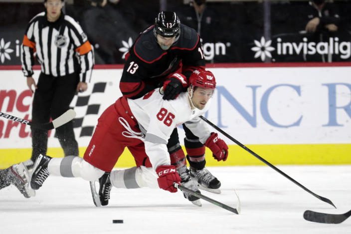 Carolina Hurricanes' Warren Foegele (13) hits Detroit Red Wings' Mathias Brome (86) as they go for the puck during the first period of an NHL hockey game in Raleigh, N.C., on Thursday, March 4, 2021. (AP Photo/Chris Seward)