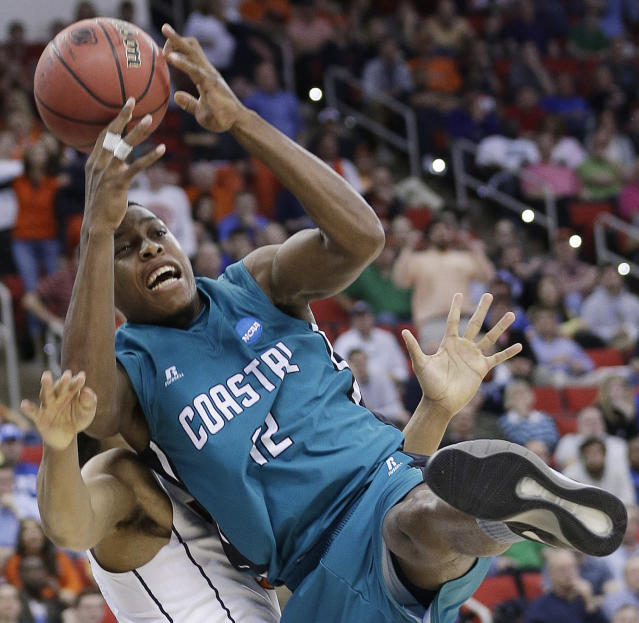 Coastal Carolina forward Michel Enanga (12) heads to the court as Virginia guard Malcolm Brogdon defends during the second half of an NCAA college basketball second-round tournament game, Friday, March 21, 2014, in Raleigh. (AP Photo/Chuck Burton)