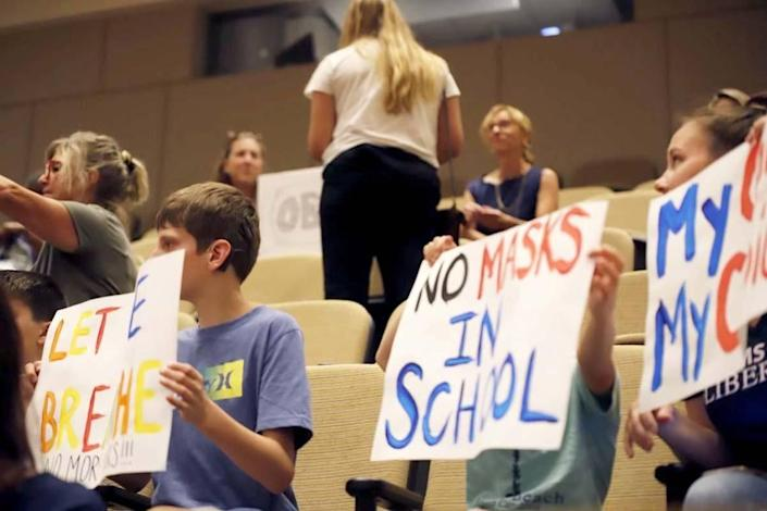 People show up with signs at the Charlotte-Mecklenburg school meeting on Friday, July 30, 2021. The board approved a recommendation to require face masks for all students and staff when classes start next month. CMS will be one of the few local districts to do so.