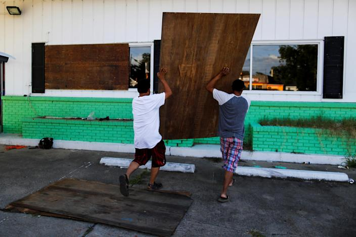 <p>People put plywood up on the windows of a theatre before the arrival of Hurricane Florence in Greenville, N.C., Sept. 12, 2018. (Photo: Eduardo Munoz/Reuters) </p>