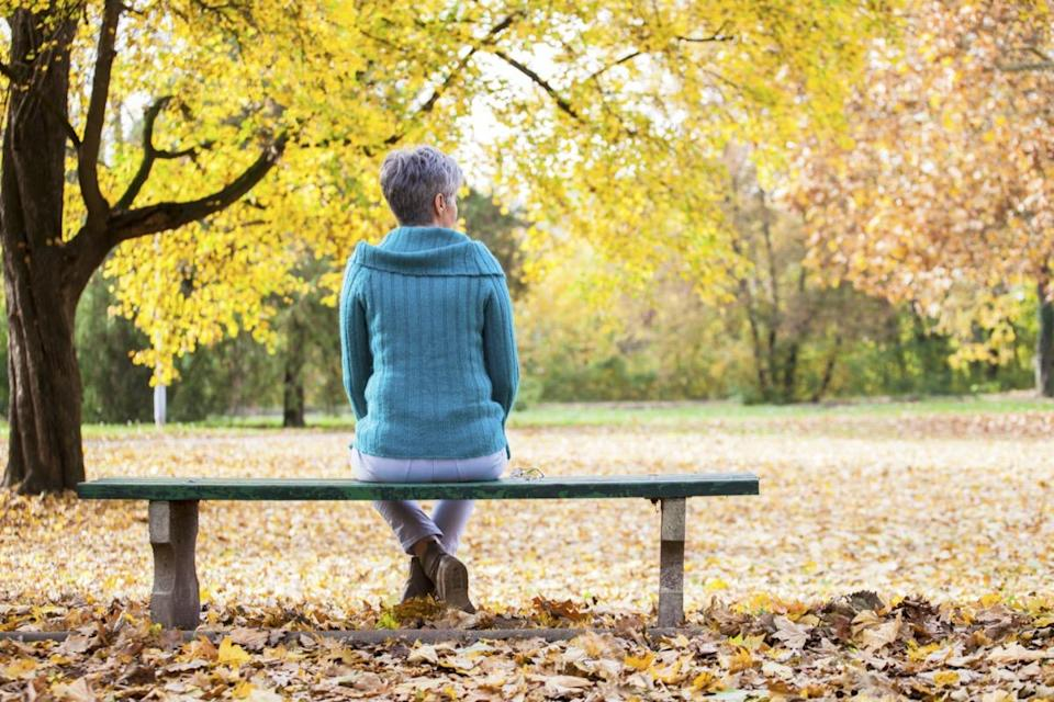 Mature woman on bench in autumn park.