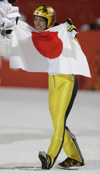 Japan's Noriaki Kasai celebrates with the Japanese flag after winning the silver during the ski jumping large hill final at the 2014 Winter Olympics, Saturday, Feb. 15, 2014, in Krasnaya Polyana, Russia. (AP Photo/Matthias Schrader)