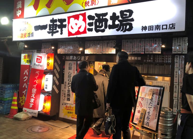 """Office workers enter """"Ikken me sakaba"""", a discount izakaya bar offering cheap food and drinks, in Tokyo"""