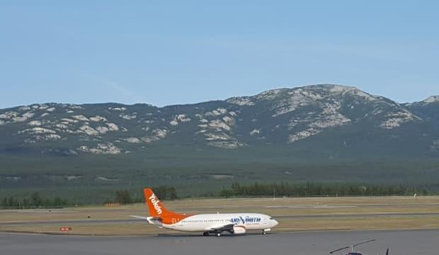An Air North plane at the airport in Whitehorse. Public health officials issued a pair of COVID-19 exposure notices Sunday for two Air North flights, traveling between Whitehorse and Vancouver. (Paul Tukker/CBC - image credit)