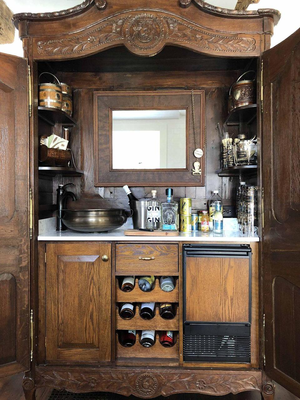 """<p>At her home in Nantucket, Boston-based designer Elizabeth Georgantas converted an antique armoire into the <a href=""""https://www.veranda.com/decorating-ideas/a29529319/guide-to-party-closets/"""" rel=""""nofollow noopener"""" target=""""_blank"""" data-ylk=""""slk:ultimate party closet"""" class=""""link rapid-noclick-resp"""">ultimate party closet</a>: a home bar that's fitted with a small sink and icemaker, along with wine storage and shelves for her vintage barware collection. </p><p><a class=""""link rapid-noclick-resp"""" href=""""https://go.redirectingat.com?id=74968X1596630&url=https%3A%2F%2Fwww.etsy.com%2Flisting%2F711942561%2Fvintage-mid-century-martini-cocktail-set%3Fgpla%3D1%26gao%3D1%26gclid%3DEAIaIQobChMIgJWU2rOg6QIViorICh1WhQYSEAYYBSABEgIyb_D_BwE&sref=https%3A%2F%2Fwww.veranda.com%2Fdecorating-ideas%2Fg28837805%2Fhome-bar-ideas%2F"""" rel=""""nofollow noopener"""" target=""""_blank"""" data-ylk=""""slk:Find Similar Vintage Barware Here"""">Find Similar Vintage Barware Here</a></p>"""