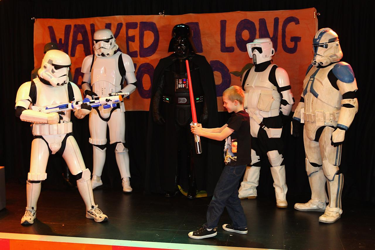 Jacob French plays with a patient after completing his trek at the Sydney Children's Hostpital on April 4, 2012 in Sydney, Australia. French today completed the over 5,000 km trek from Perth to Sydney on foot, donning a full body stormtrooper costume he successfully raised over $100,000 for the Starlight Children's Foundation. Since July 2011, Jacob has walked 10 hours a day, Monday to Friday, lost over 12kg in weight, and gone through seven pairs of shoes. The Starlight Children's Foundation provides programs to help lift the spirits of sick children in hospitals accross Australia.  (Photo by Cameron Spencer/Getty Images)