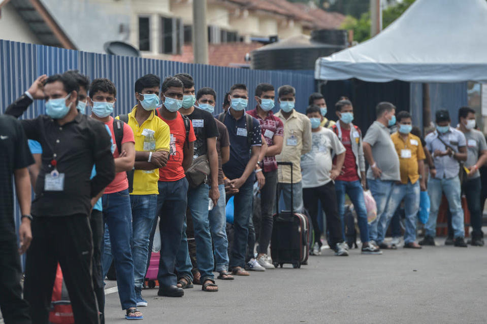 Top Glove workers lining up outside workers' dormitories to be taken to Covid-19 quarantine centres November 26,  2020. — Picture by Miera Zulyana