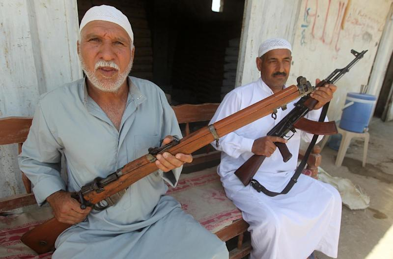 Iraqi men carry their weapons in Jdaideh in Diyala province on June 14, 2014 following the the call to arms by Shiite cleric Grand Ayatollah Ali al-Sistani (AFP Photo/Ahmad al-Rubaye)