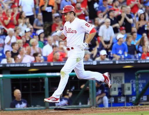 Philadelphia Phillies' Chase Utley scores on a RBI single by Ryan Howard during the first inning of a baseball game with the Atlanta Braves, Friday, July 5, 2013, in Philadelphia. (AP Photo/Tom Mihalek)