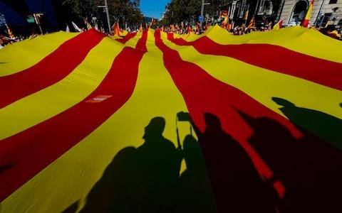 People hold a giant Catalan Senyera flag as protesters gather ahead of a pro-unity demonstration  - Credit: PIERRE-PHILIPPE MARCOU/AFP/Getty Images