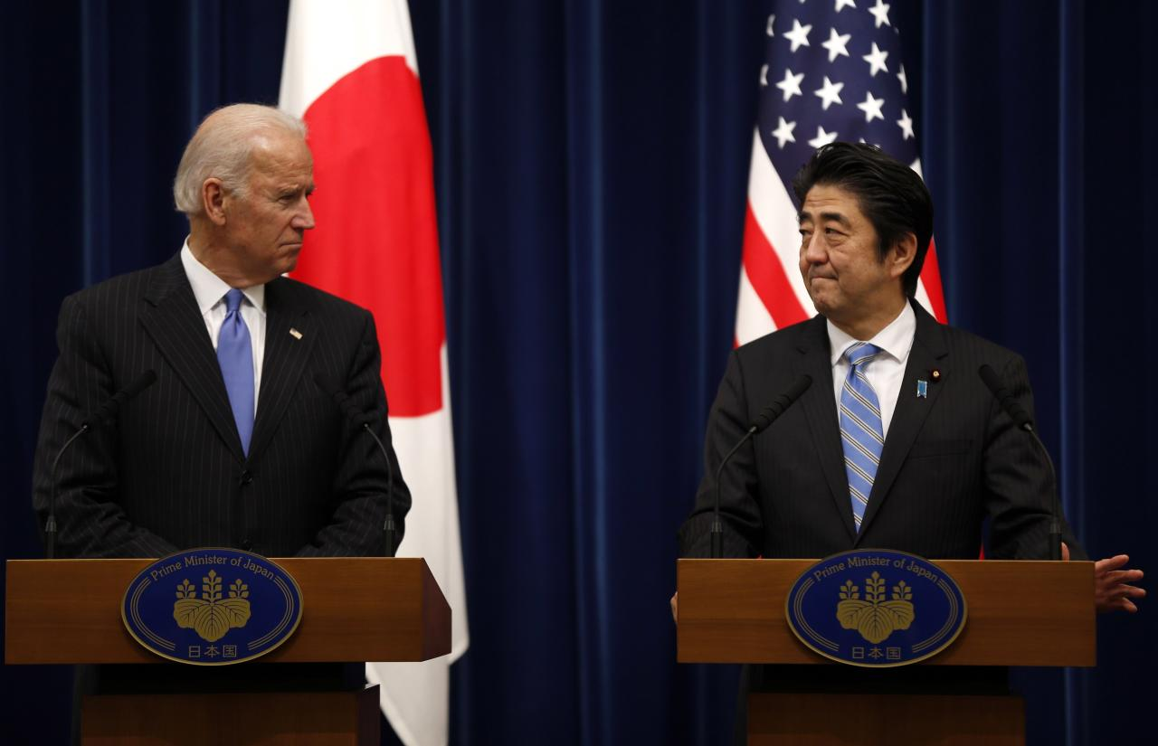 U.S. Vice President Joe Biden (L) and Japan's Prime Minister Shinzo Abe attend a joint news conference following their meeting at the prime minister's official residence in Tokyo December 3, 2013. Biden urged Japan and China to lower tensions that have spiked since Beijing announced an air defense zone over disputed islands in the East China Sea, while repeating that Washington was worried by the move. REUTERS/Toru Hanai (JAPAN - Tags: POLITICS)
