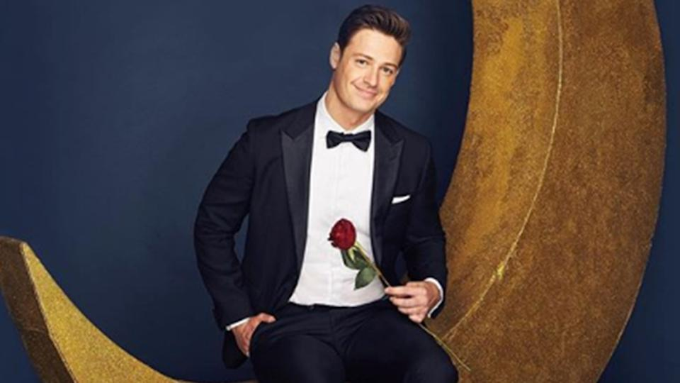 A photo of The Bachelor Australia 2019, Matt Agnew, wearing a suit and holding a rose while sitting on a crescent moon prop. Photo: Channel 10.