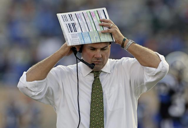 Miami coach Al Golden listens on his headset during the first half of an NCAA college football game against Duke in Durham, N.C., Saturday, Nov. 16, 2013. Duke won 48-30. (AP Photo/Gerry Broome)
