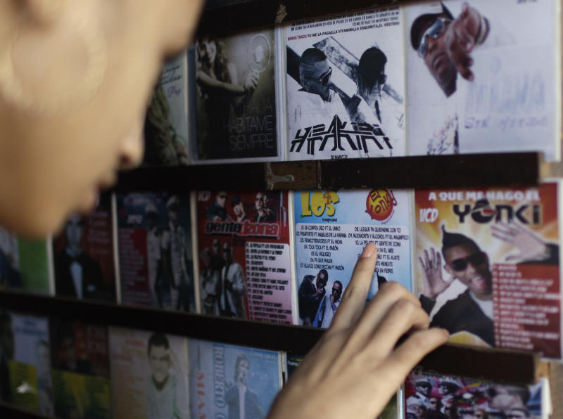 """In this Jan. 4, 2013 photo, Yadisbel Ruiz, 17, reads the titles of songs on a reggaeton album at a music and movie store run from a home in Havana, Cuba. Cuban authorities have recently announced restrictions reportedly declaring state-run recording studios and broadcasts off-limits to songs with questionable lyrics. They also prohibit such music in performance spaces subject to government control. The rules would theoretically apply to all genres, but it's reggaeton that leading cultural lights have singled out for criticism in official media while warning of new rules governing """"public uses of music."""" (AP Photo/Franklin Reyes)"""